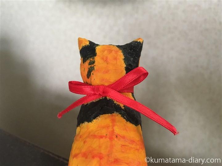 鈴をつけた木彫りの三毛猫さん後ろ姿
