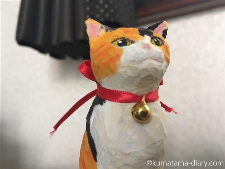 鈴をつけた木彫りの三毛猫さん顔