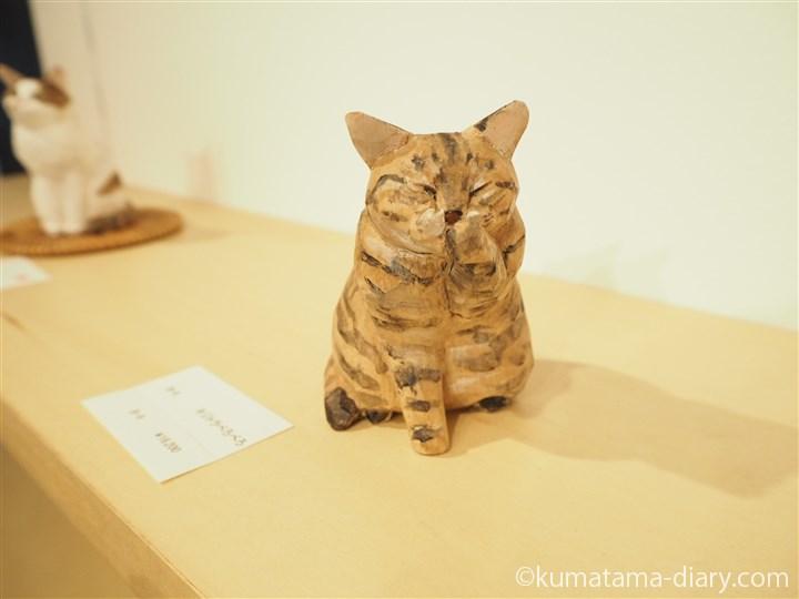 前足をなめるキジトラ猫