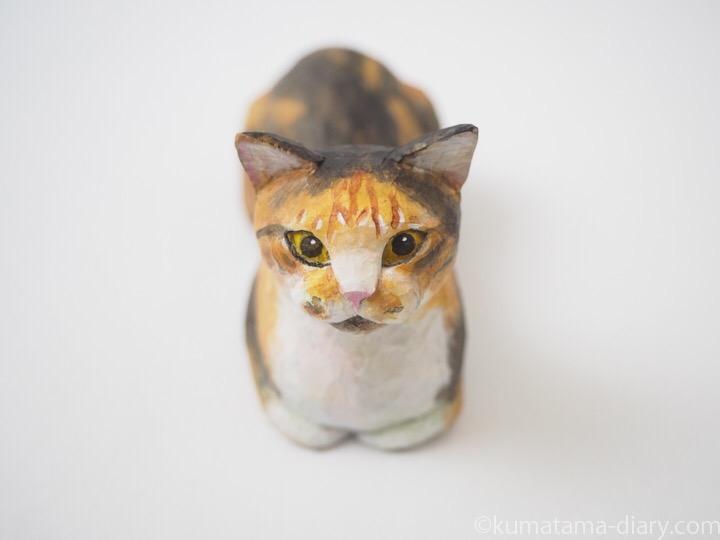 香箱を組む三毛猫の木彫り猫