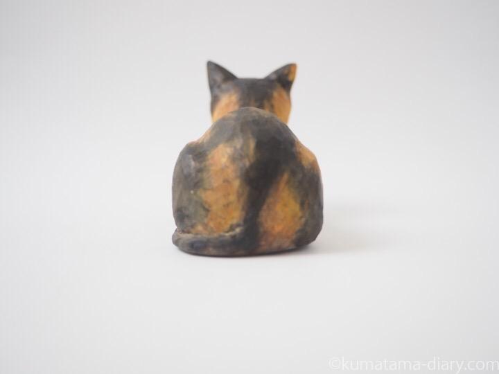 香箱を組む三毛猫の木彫り猫後ろ
