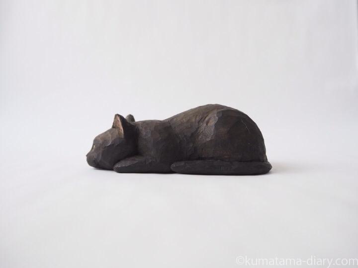 寝そべる黒猫木彫り猫左