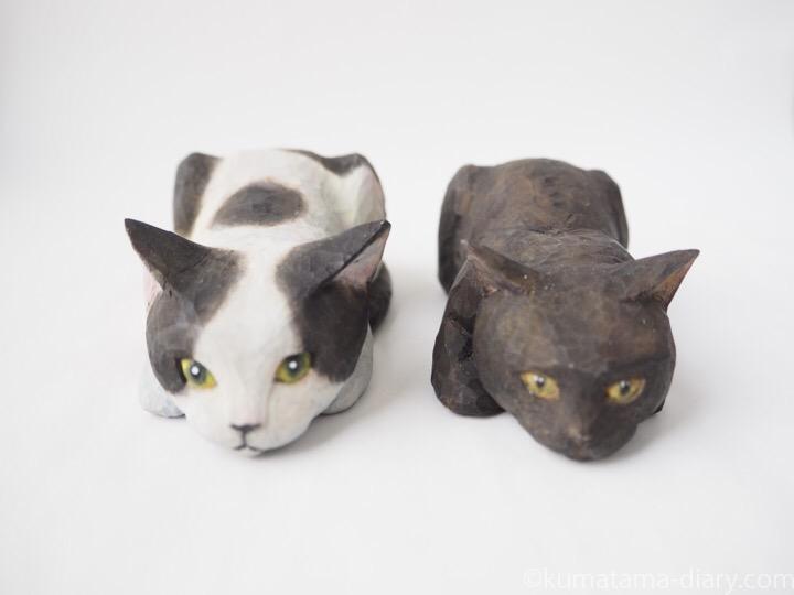 寝そべる木彫り猫白黒猫と黒猫